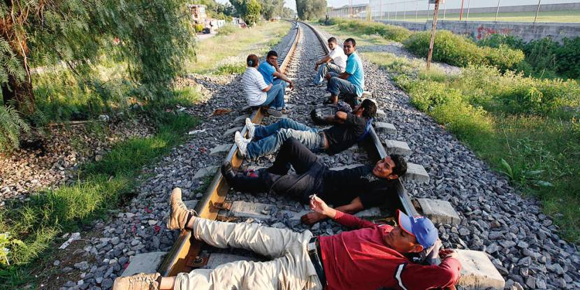 Illegal migrants rest on a railway line in Huehuetoca, August 2, 2012. Hundreds of Central American migrants on their way to the United States are now forced to seek shelter in the open air due to the closure of an important migrants' shelter in the state. The San Juan Diego shelter in Lecheria was temporarily closed earlier this month by church authorities because of complaints by neighbours who said the migrants had become disruptive to the neighbourhood and were contributing to insecurity in the area, which is located along the train tracks that many migrants use to travel north. Days after, a temporary shelter, located under a bridge near the suburban train station, was opened but neighbourhood organizations also requested its closure. REUTERS/Edgard Garrido (MEXICO - Tags: SOCIETY IMMIGRATION POLITICS TPX IMAGES OF THE DAY) - GM2E8830YNO01